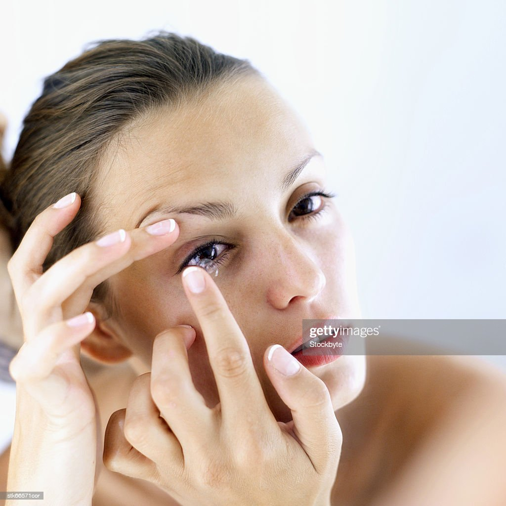 woman putting in contact lens : Stock Photo