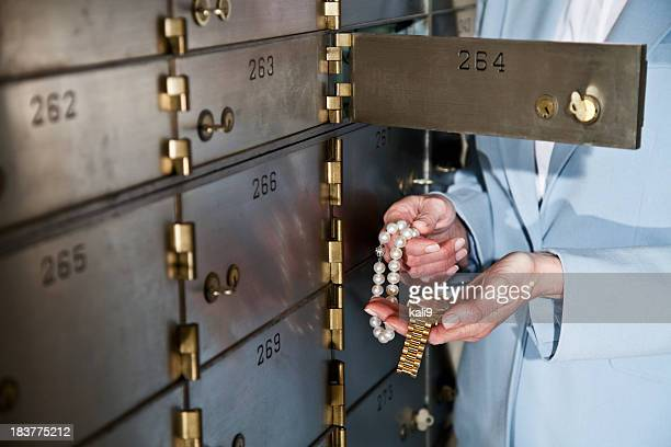 Woman putting jewelry in safety deposit box