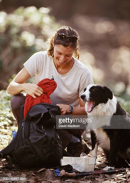 Woman putting jumper in bag by Border Collie dog, outdoors