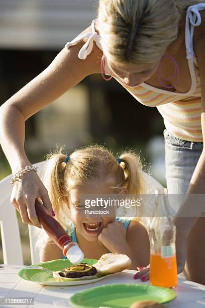 A woman putting ketchup on a young girl's burger