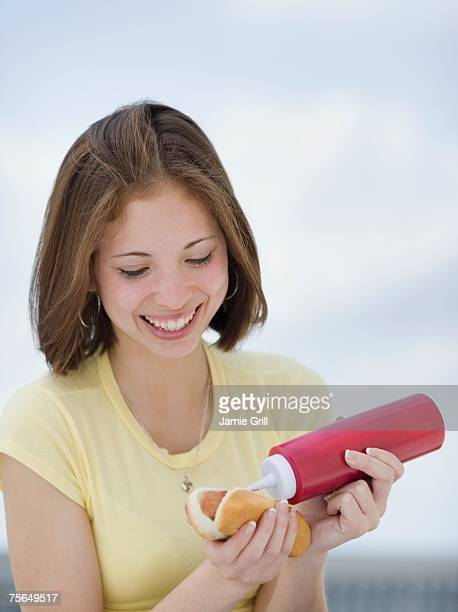 Woman putting ketchup on hotdog