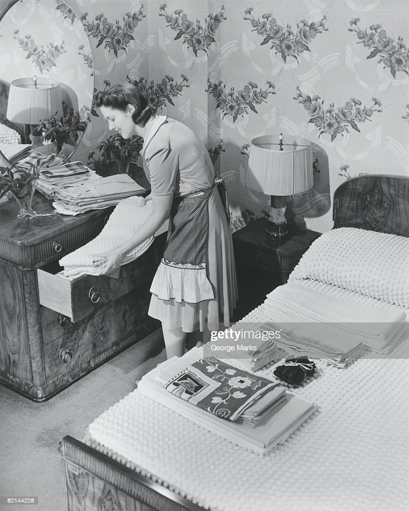 Woman putting linen to drawer, (B&W) : Stock Photo