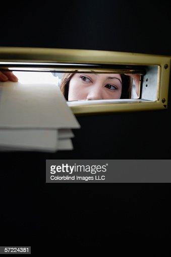 Woman putting mail through slot : Stock Photo