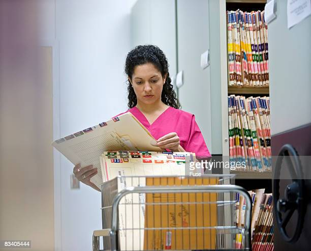 Woman Putting Medical Records in Cart