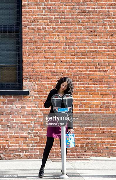 Woman putting money in parking meter