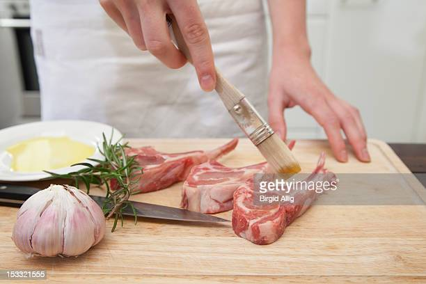 Woman putting oil on lamb chops