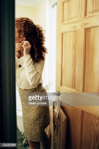 Woman putting on earrings in bathroom