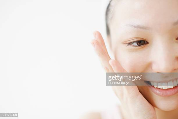 Woman putting on face lotion, smiling