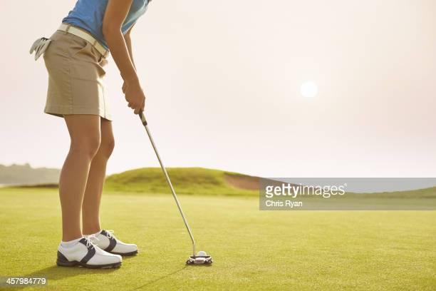 Femme mettant sur le parcours de golf