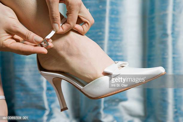 Woman putting on high heeled shoe, close up of foot