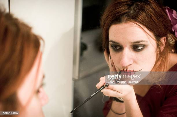 Woman putting on make up for Halloween party