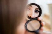 Woman putting on mascara in compact mirror