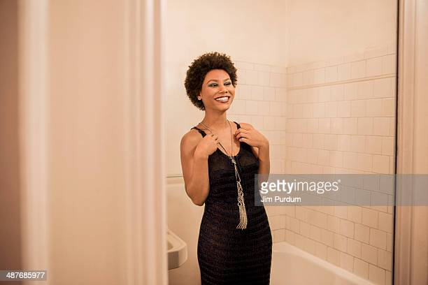 Woman putting on necklace in bathroom