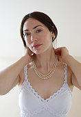 Woman putting on necklace of pearls.