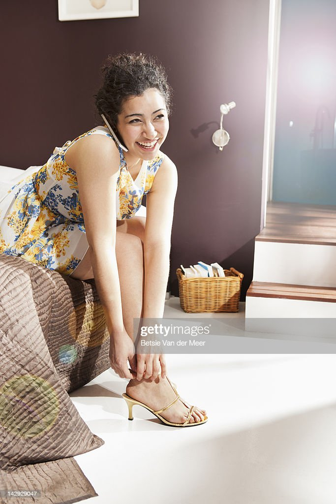 Woman putting on shoes, while on phone. : Stock Photo