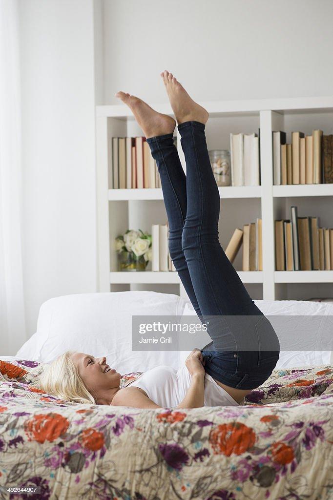 Teenage Girl Lying On Bed Holding Mobile Phone Portrait