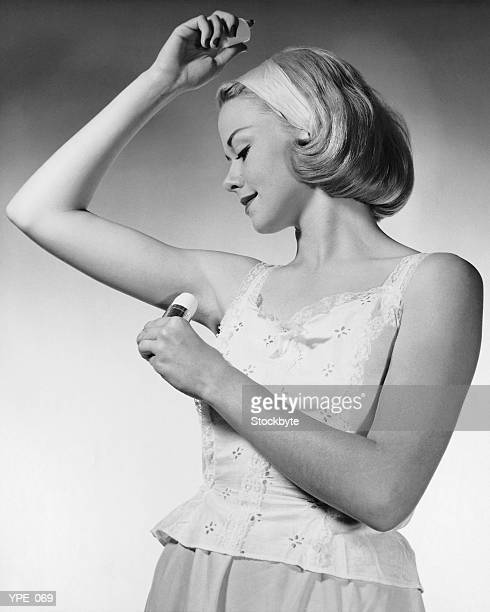 Woman putting on underarm deodorant