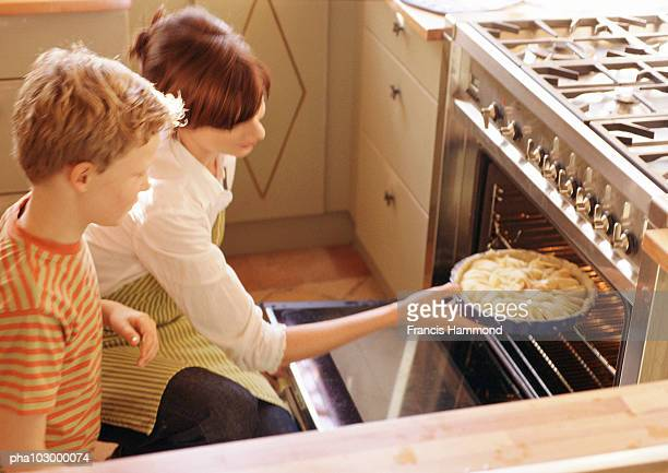 Woman putting pie in oven
