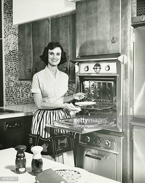 Woman putting pie into oven in kitchen, (B&W), portrait
