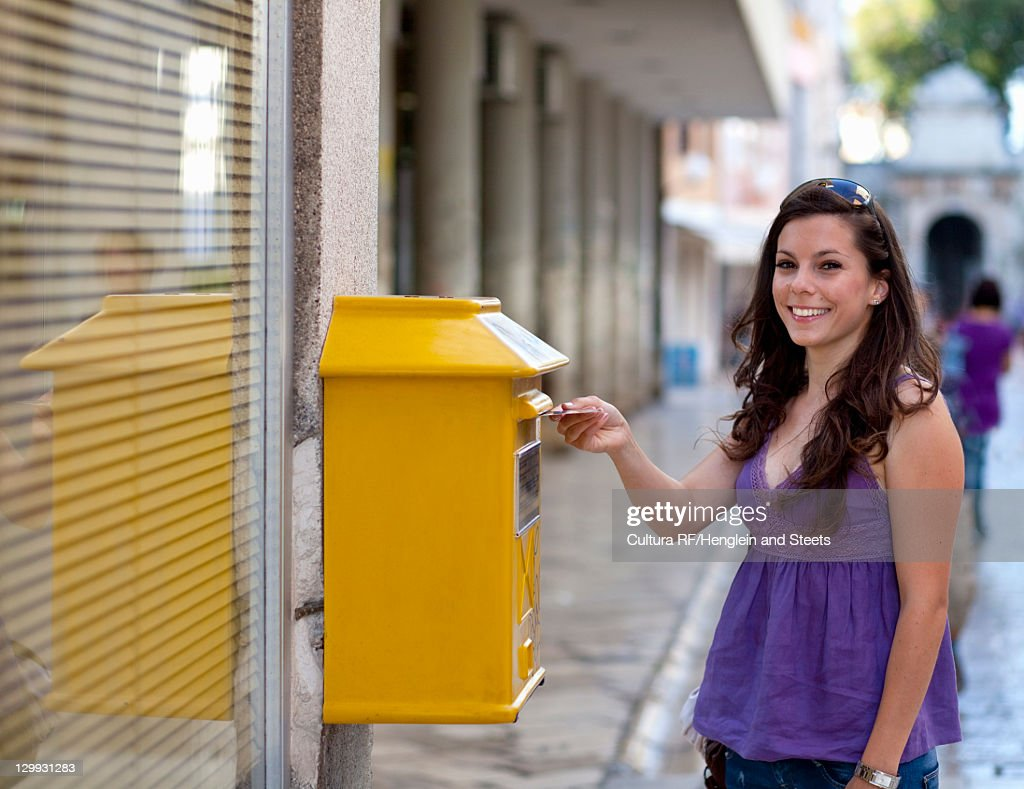 Woman putting postcard in mailbox : Bildbanksbilder