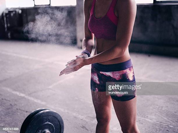 Woman putting powder on her hands preparing for lifting weights