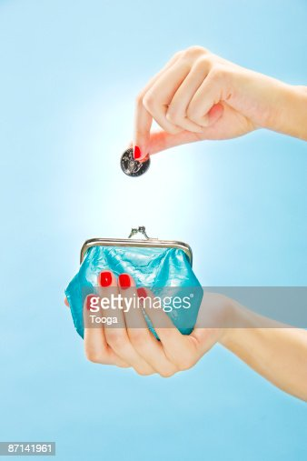 Woman putting quarter in change purse : Bildbanksbilder