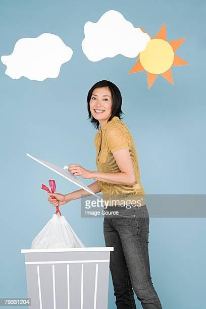 Eine Frau putting Abfälle in einen Behälter