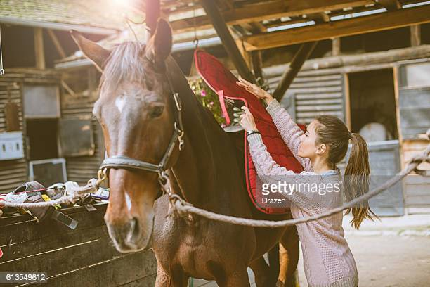 Woman putting saddle on her horse