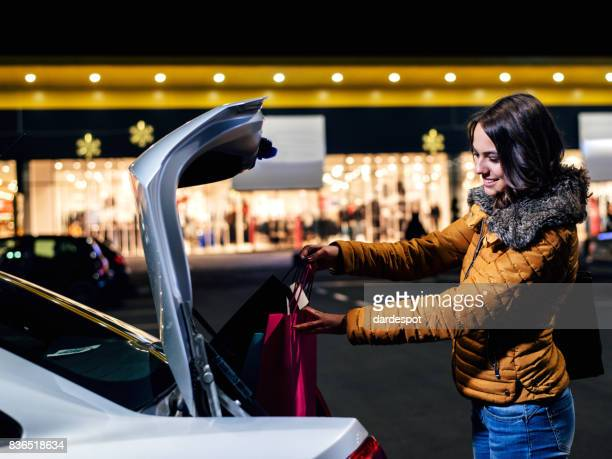 Woman putting shopping bags in the car