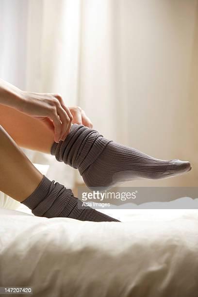 woman putting socks on feet