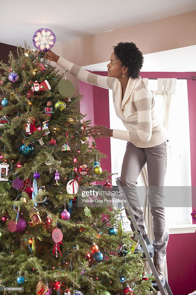 Woman putting star on top of Christmas Tree : Stock Photo