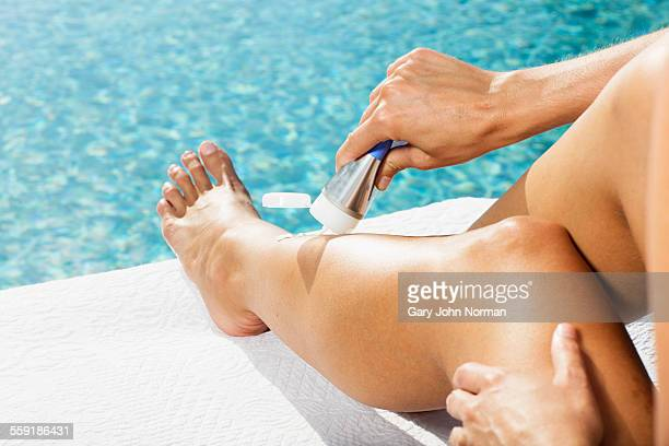 Woman putting sun cream on her legs, close up.