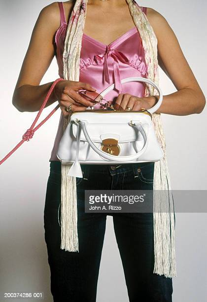 Woman putting sunglasses in purse, mid section