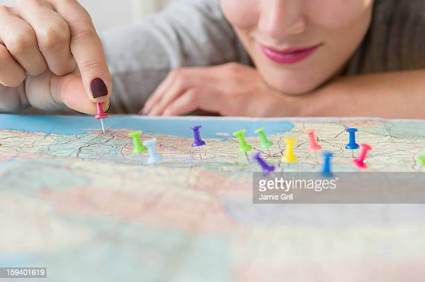 Woman putting tacks in map