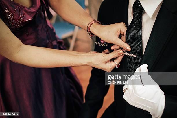 Woman putting tie pin