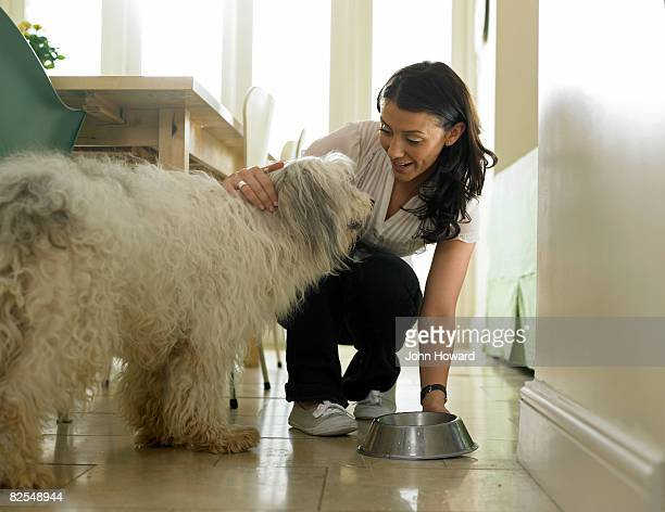 Woman putting water bowl down for her dog