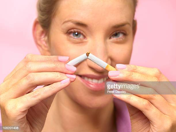 Woman quitting smoking by braking cigarette