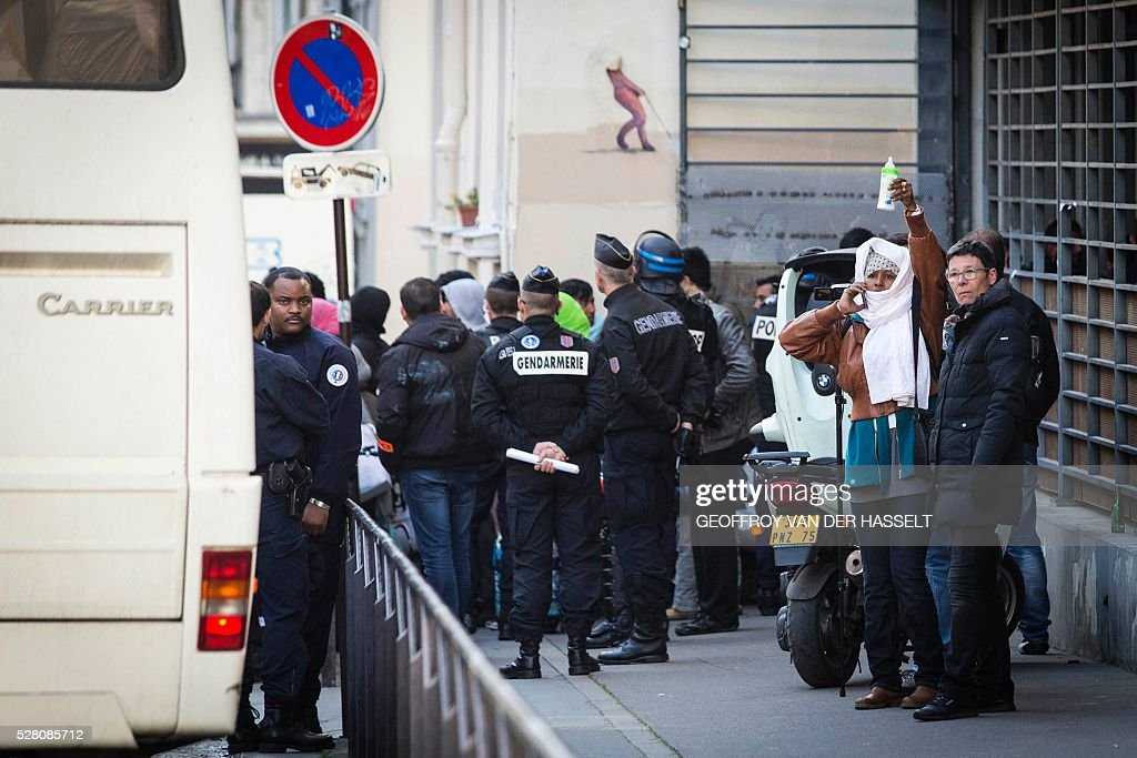 A woman raises a baby bottle as migrants evacuate an occupied highschool under the police supervision in Paris on May 4, 2016. A highschool under construction occupied by 200 migrants in northeatern Paris since two weeks has been evacuated this morning by the police, while protesters clashed with policemen outside the building. / AFP / GEOFFROY