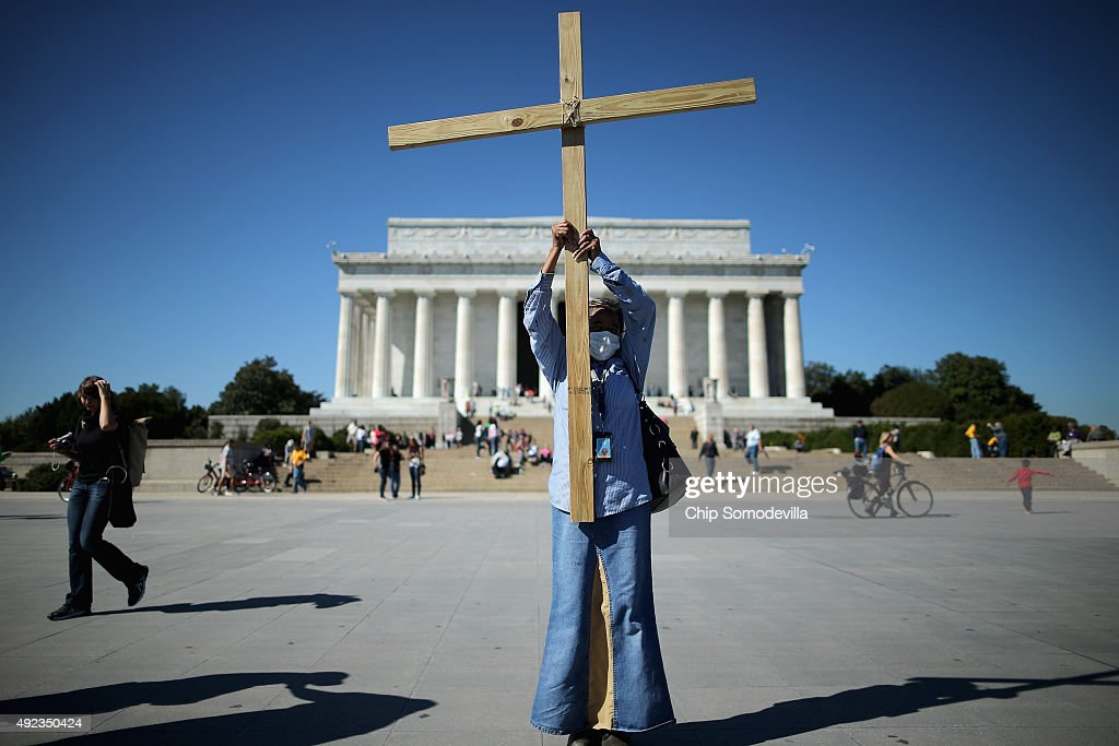 A woman raises a wood cross in praise during the second annual Washington Prayer Gathering on the National Mall October 12 2015 in Washington DC...