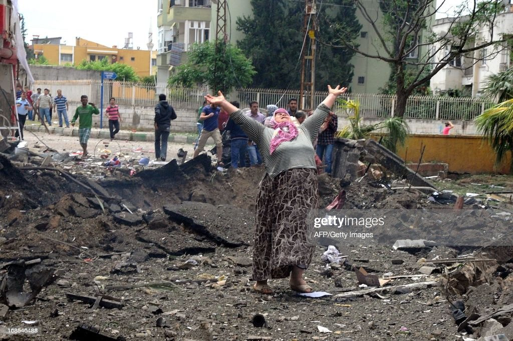 A woman raises her arms and shouts as she stands on the site where car bombs exploded on May 11, 2013 near the town hall in Reyhanli, just a few kilometres from the main border crossing into Syria, killing four people and wounded another 18, according to an initial toll.