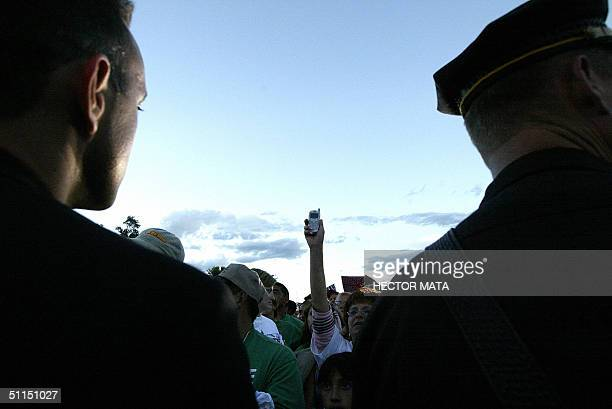 A woman raises her celphone to make her relatives listen to the speech of Democratic Presidential Candidate John Kerry in Las Vegas New Mexico 07...