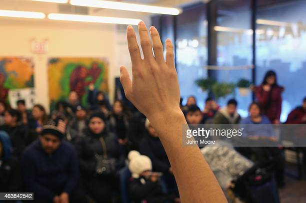 A woman raises her hand as Immigrants attend a workshop for Deferred Action for Childhood Arrivals on February 18 2015 in New York City The immigrant...