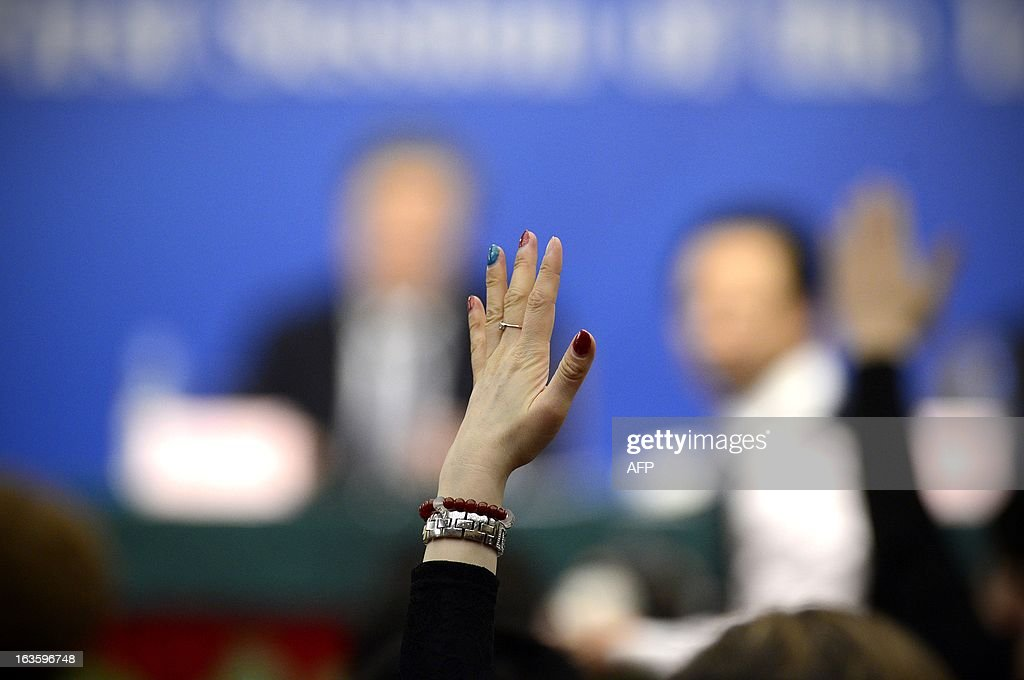 A woman raises her hand as she prepares to ask a question during a press conference in the first session of the 12th National People's Congress (NPC) in Beijing on March 13, 2013. Thousands of delegates from across China meet this week to seal a power transfer to new leaders whose first months running the Communist Party have pumped up expectations with a deluge of propaganda.