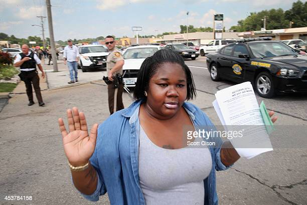A woman raises her hands as she walks by police shortly after they arrested a demonstrator protesting the killing of teenager Michael Brown on August...