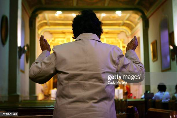 A woman raises her hands in prayer in the Iglesia de la Placita at Nuestra Senora Reina de Los Angeles or Our Lady Queen of Angeles Church March 31...