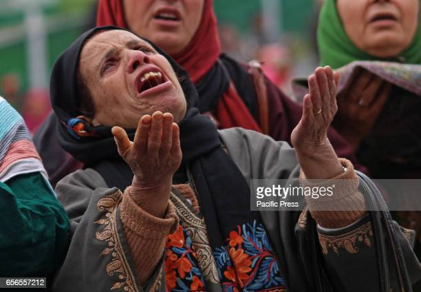 A woman raises her hands towards the holy relic being displayed by the priest of the famous Hazratbal Shrine in Indianadministered Kashmir's capital...
