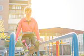 beautiful athletic woman lifts up legs building abs muscles on parallel bars