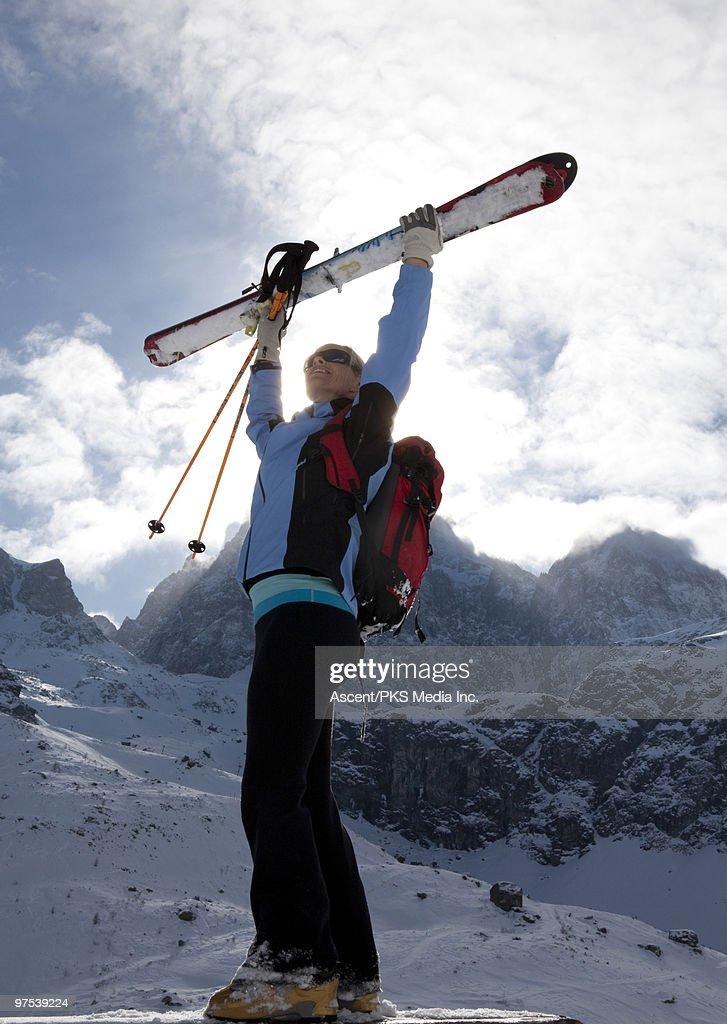 Woman raises skis overhead, mountain behind : Stock Photo