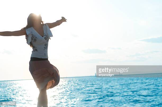 Woman raising arms into the sky at the seaside