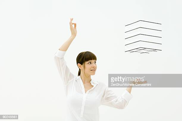 Woman raising arms, looking up at cube floating in midair